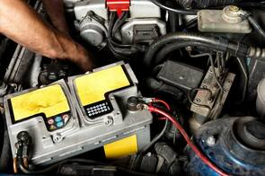 Auto electrician replacing a battery inside and engine bay